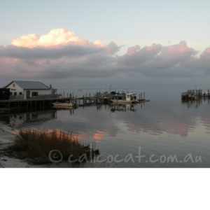 Photo of a house and jetty, clouds and water